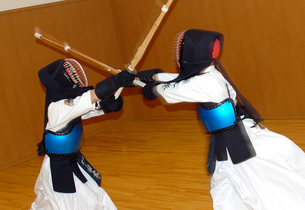 Two children engage in kendo training together, they are part of the same dojo and are practicing simultaneous striking.