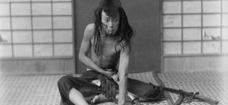 Kabuki player performing a bandit who is committing Harakiri