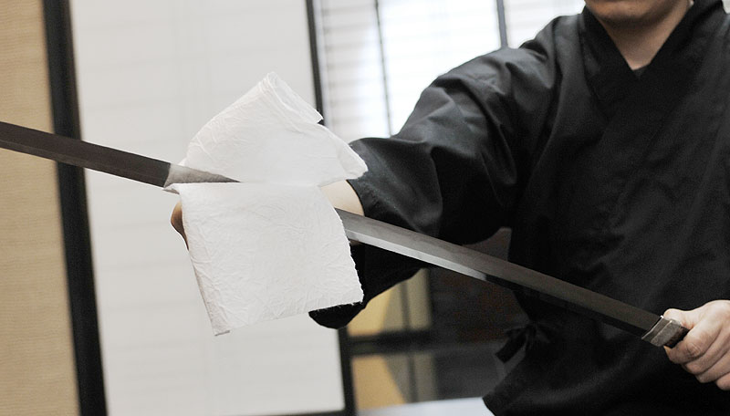 Wiping Japanese sword blade with Japanese paper
