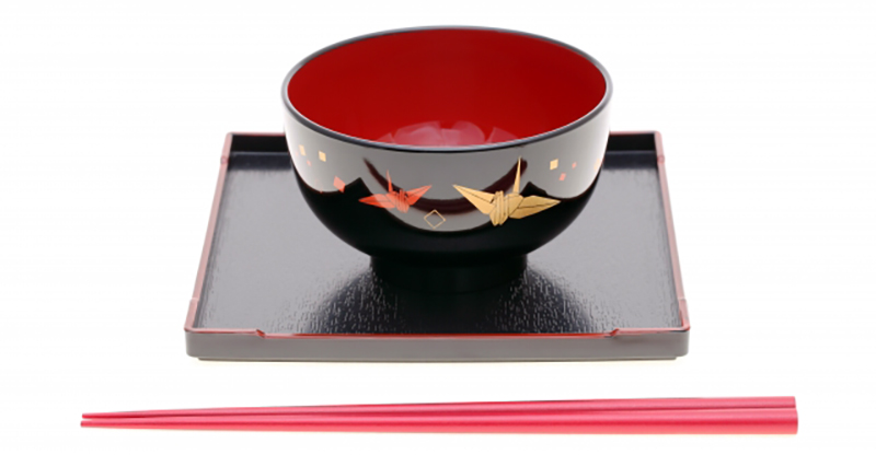 A lacquerware rice bowl featuring an origami crane relief.
