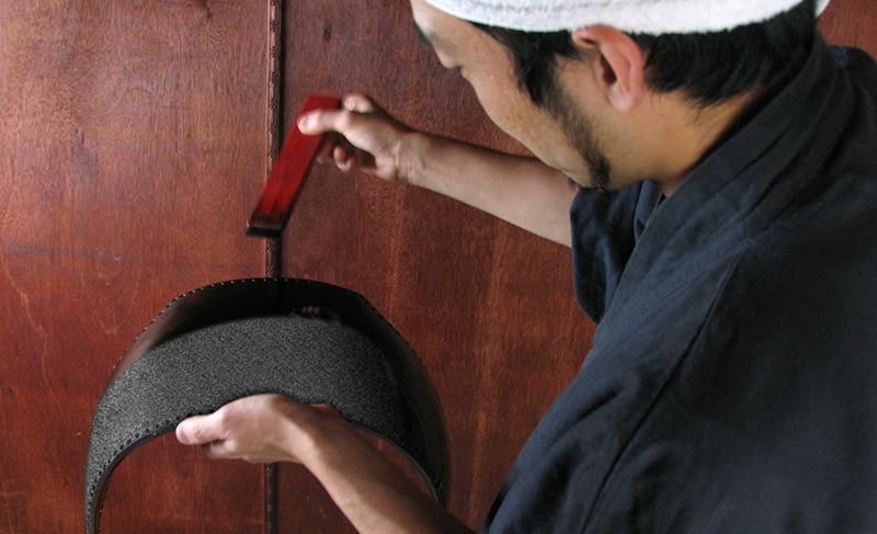 A craftsmen applying urushi lacquer to a dodai with a brush.