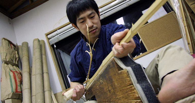 Tozando Shinai craftsman shaving bamboo staves.