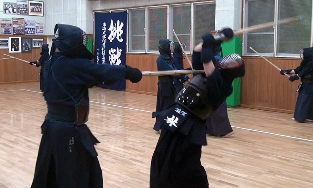 A kendo student receives a powerful thrust to the throat when attempting to strike their teacher.