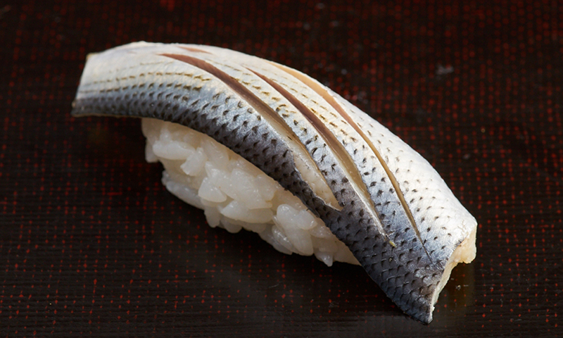 A single piece of Konoshiro nigiri sushi, the chef has made three incisions across its spotted skin.