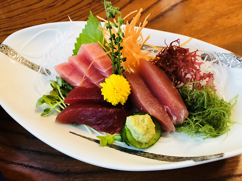 Cuts of tuna sashimi arranged with vegetables and a flower on a serving plate.