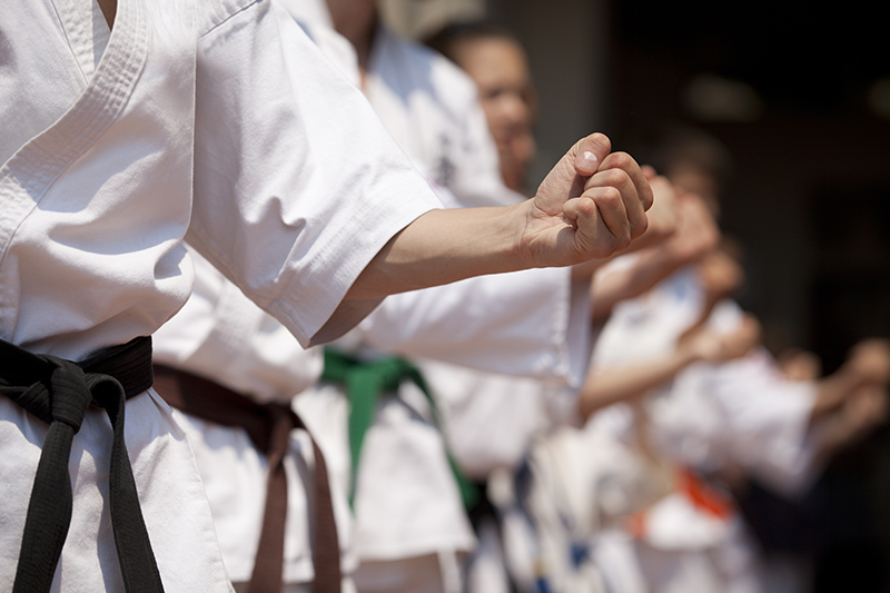 A close up of Karate practioners practicing; they are practicing forms being led by a blackbelt, the others are wearing belts of different colours.