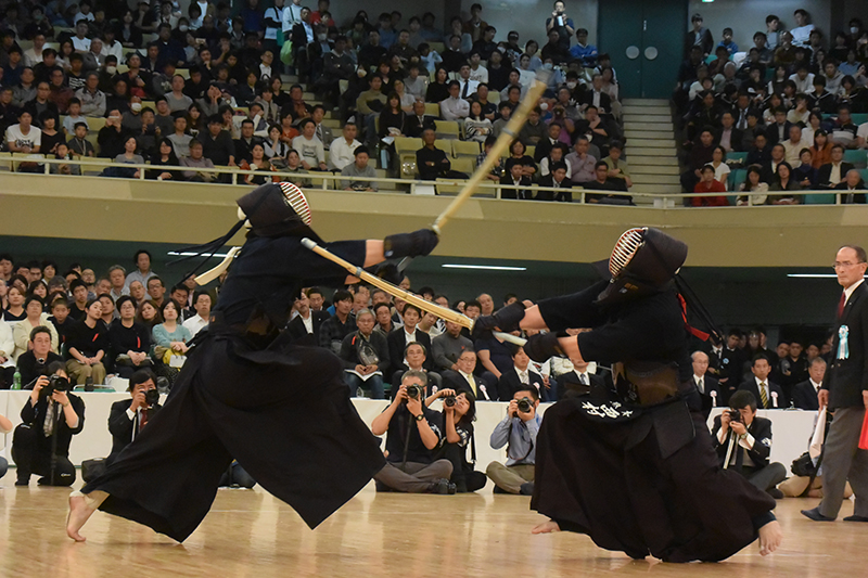 Two kendoka face each other during a shiai; one tries to strike kote and another tries to strike men.