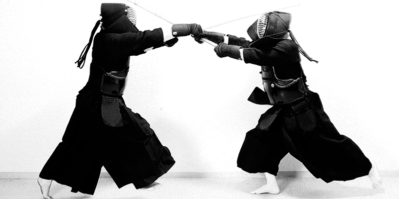 Black and white photo of two Kendo players trying to hit the Men