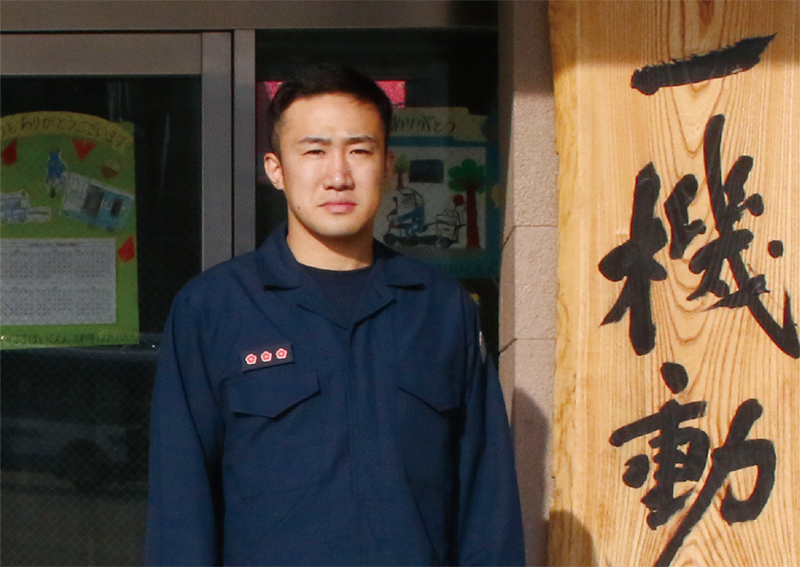 Kunitomo standing in front of Police Department