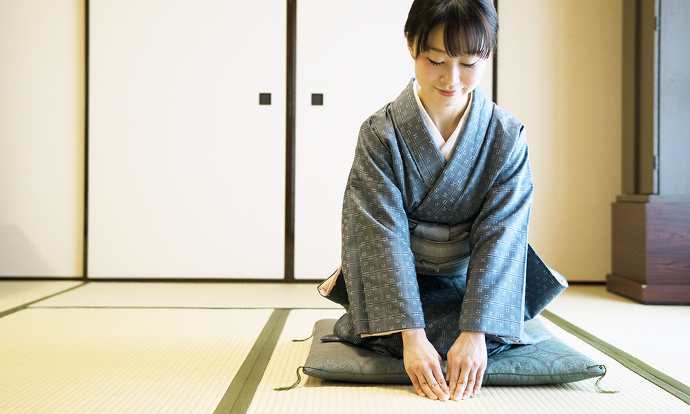 Kimono-wearing Japanese lady greeting in a traditional Japanese room